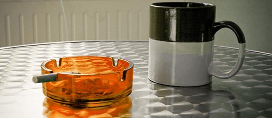 oranžový popolník a cigareta položené vedľa šálky