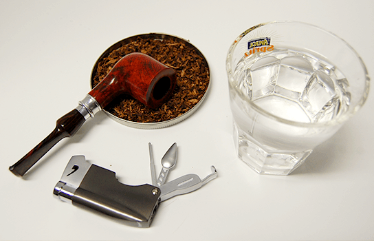 fajka, fajkový tabak, fajkový zapaľovač s príborom a pohár vody na bielom stole