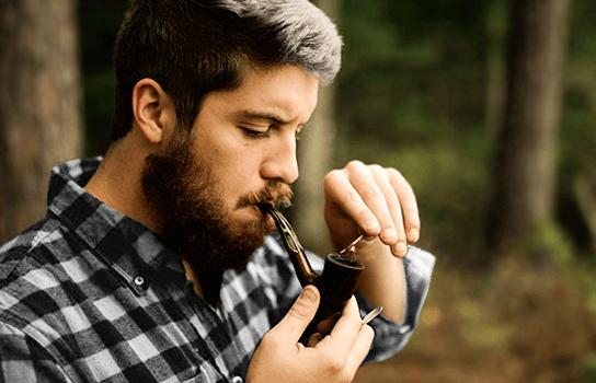 mladý muž fajčí fajku na tabak
