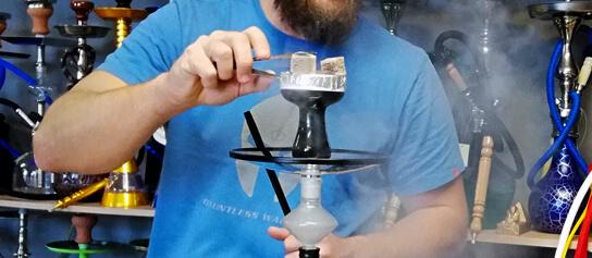muž fajčiaci vodnú fajku, uhlíky na korunke, dym