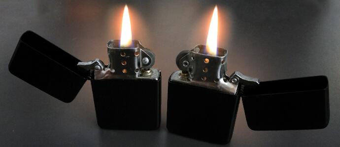 dva zapaľovače značky zippo s horiacimi plameňmi