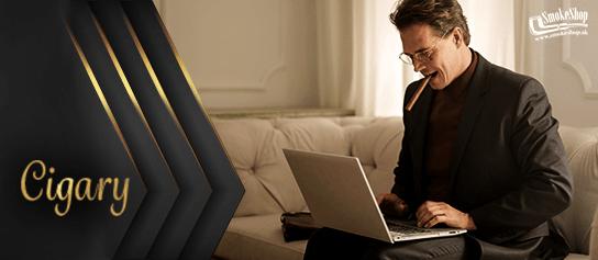 elegantná muž sedí pri laptope a fajčí cigaru